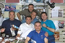 The two crews share a meal on ISS.
