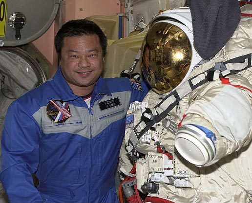 Chaio poses with a U.S. EVA suit. Image credit NASA