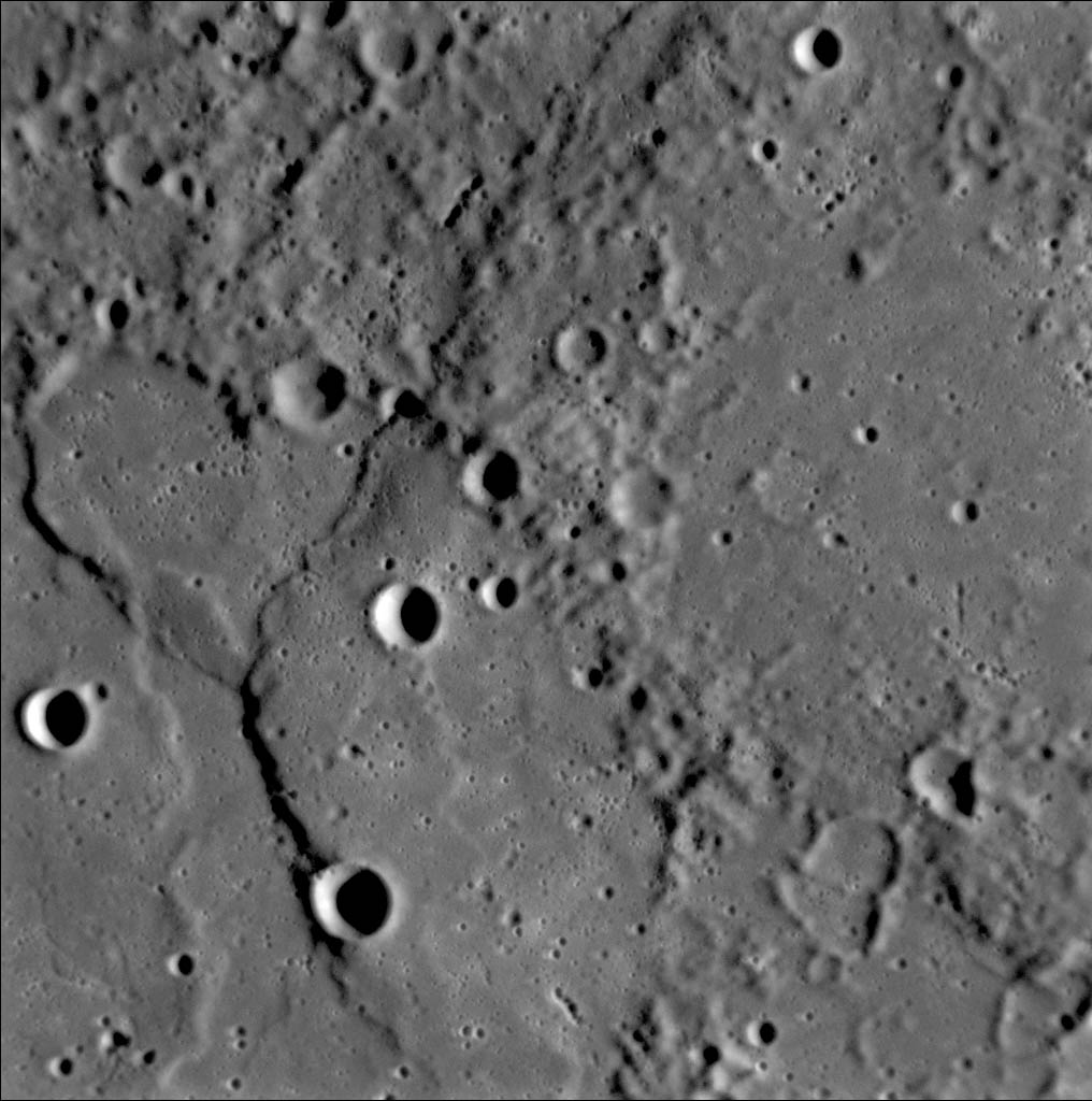 One of the first photos taken of Mercury's surface by the MESSENGER probe, showing ridges and cliffs along with craters.
